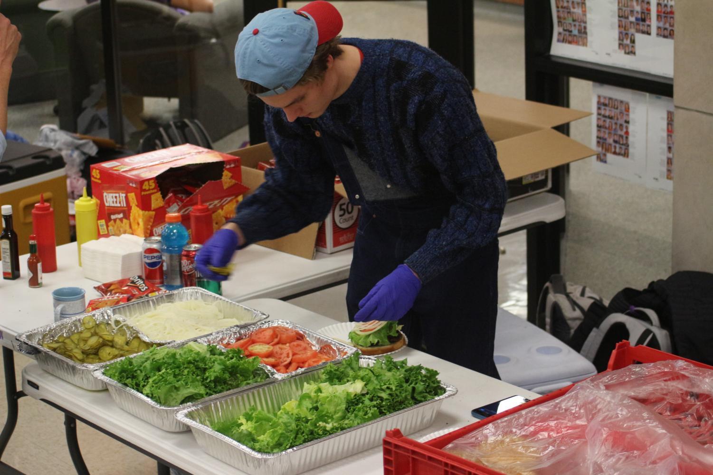 Joe Holtsford prepares Billiard's burgers at his table for the Charity Fair.